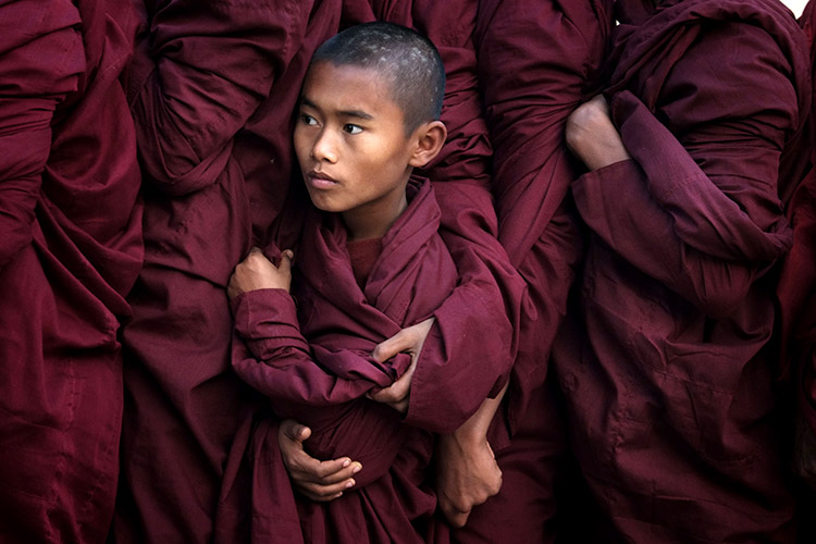 Myanmar, Bagan, © Alain Schroeder At 7AM during the annual festival of Ananda Pagoda in Bagan, monks line up to receive alms prepared by devotees who have journeyed from all corners of the country. A young monk finds himself stuck in between his brothers in the shuffle.